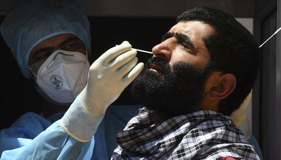 Un trabajador de la salud toma una muestra de un hisopo nasal de un hombre para realizar la prueba del coronavirus en India. (Foto: AFP)