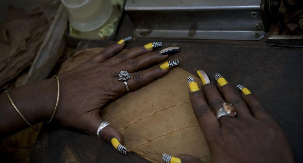 Una trabajadora con las uñas pintadas con colores alusivos al cigarro Cohiba alista hojas de tabaco para hacer cigarros en la fábrica El Laguito, mientras en La Habana, Cuba, se festeja el Festival del Habano, el 21 de febrero del 2019. (AP Foto/Ramón Espinosa)