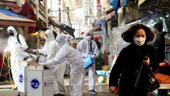 Una mujer que usa una mascarilla para evitar contraer el coronavirus reacciona cuando los empleados de una empresa de servicios de desinfección desinfectan un mercado tradicional en Seúl, Corea del Sur. 26 de febrero de 2020. REUTERS/Kim Hong-Ji.