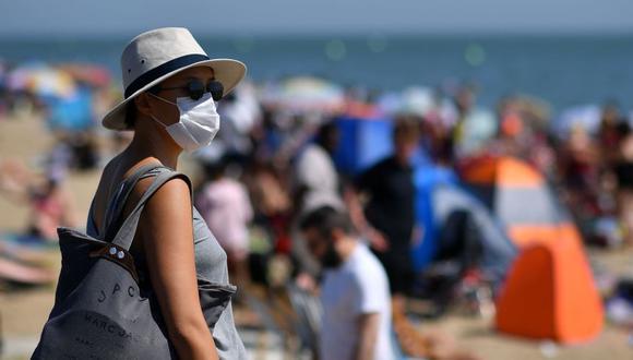 Una mujer usa una mascarilla para protegerse del coronavirus COVID-19 a su llegada a la playa en el mar en Southend on Sea, al sudeste de Inglaterra. (Foto: AFP / Ben Stansall)