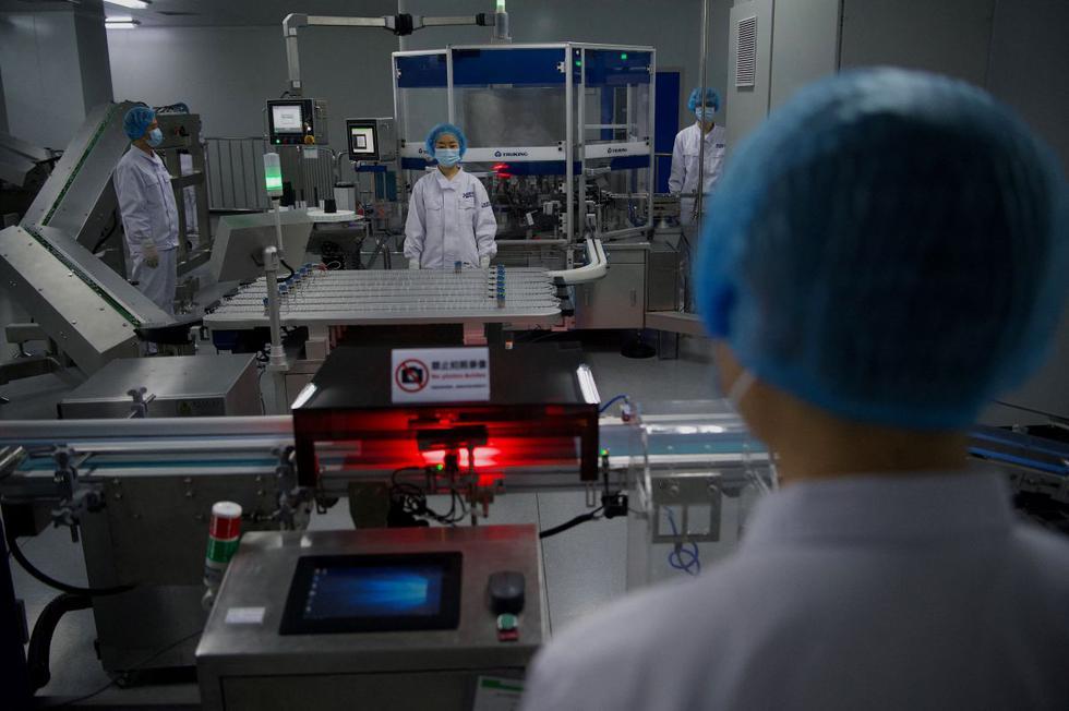 El presidente de la farmacéutica estatal china Sinopharm, Liu Jingzhen, anunció este viernes que la compañía prevé producir este año 1.000 millones de dosis de su vacuna inactivada contra el coronavirus, una buena parte de ellas destinadas a la exportación. Imagen de trabajadores en el taller de envasado en Beijing. (Texto: EFE / Foto: AFP).