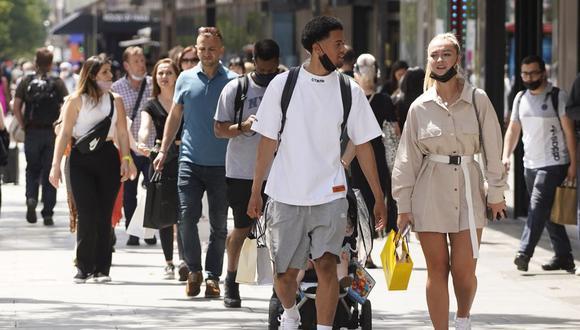 Peatones, algunos con cubiertas faciales debido al coronavirus, pasan frente a las tiendas de Oxford Street en el centro de Londres, Reino Unido, el 7 de junio de 2021. (Niklas HALLE'N / AFP).