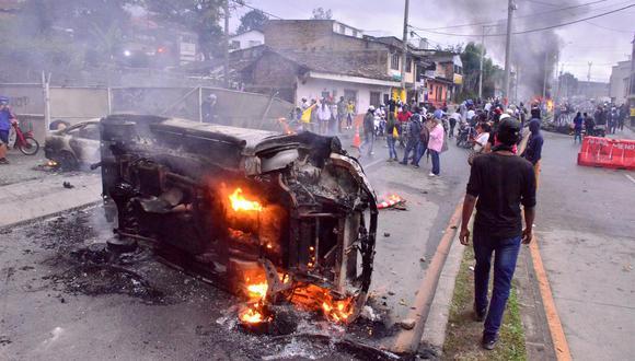Un hombre camina junto a un carro incinerado en la ciudad de Popayán este viernes, luego de una nueva jornada de protestas al cumplirse un mes del inicio del Paro Nacional en Colombia. (EFE/ Mario Parra)