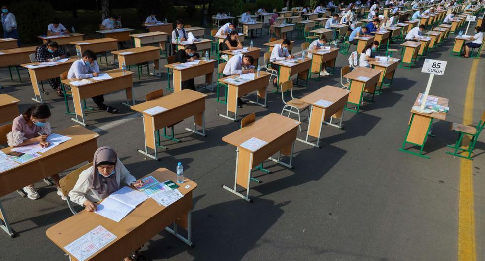 FOTO 1 | Varios estudiantes uzbekos realizan un examen en plena calle en la capital Taskent. (Photo by YURI KORSUNTSEV/AFP via Getty Images)