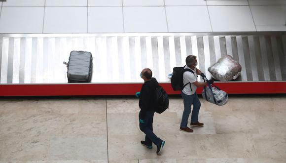 Pasajeros que acaban de aterrizar en el Aeropuerto Adolfo Suárez-Madrid Barajas (España) esperan con mascarillas a recoger sus maletas en la sala de equipaje. (Foto: Sergio Perez / Reuters).