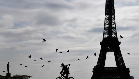 En esta foto de archivo tomada el 22 de marzo de 2020, un policía en bicicleta se va después de realizar controles a las personas en la explanada del Trocadero, cerca de la Torre Eiffel, en París (Francia). (FRANCK FIFE / AFP).