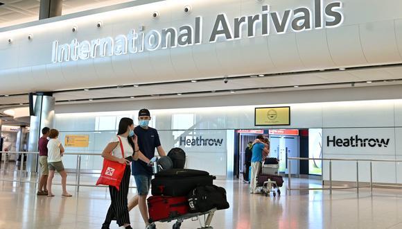 Pasajeros que usan PPE (equipo de protección personal), incluida una máscara facial como medida de precaución contra COVID-19, caminan por la sala de llegadas después de aterrizar en la Terminal Dos del Aeropuerto Heathrow de Londres. (Foto: AFP)