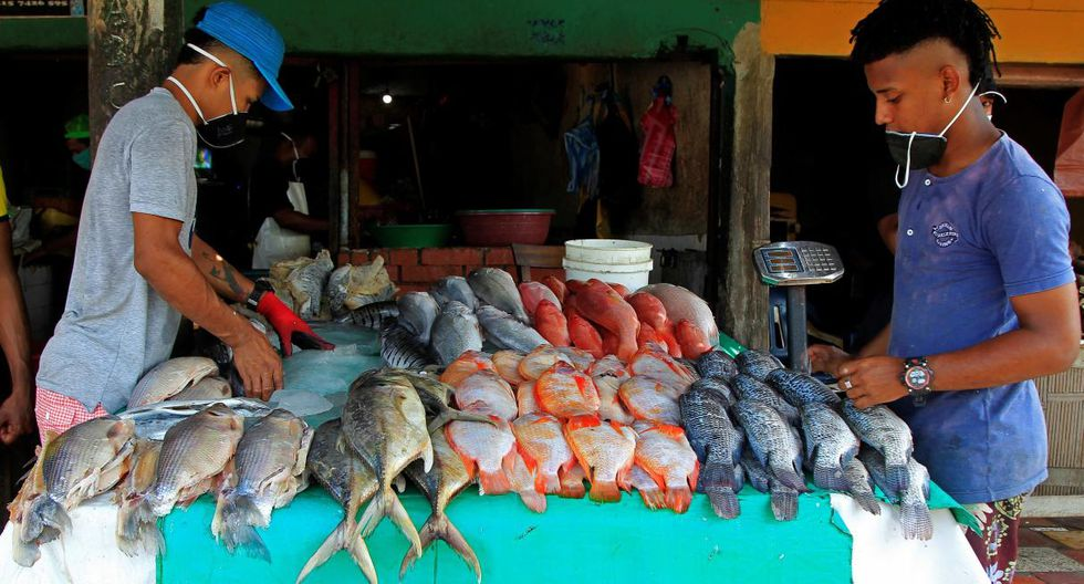 Dos jóvenes venden pescado en el mercado de Bazurto, principal centro de acopio de Cartagena de Indias (Colombia). (EFE/ Ricardo Maldonado Rozo).