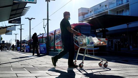 Un hombre sale de un supermercado en Canberra el 12 de agosto de 2021, tras la orden de confinamiento por coronavirus decretada por el gobierno de Australia. (Foto de Rohan THOMSON / AFP).