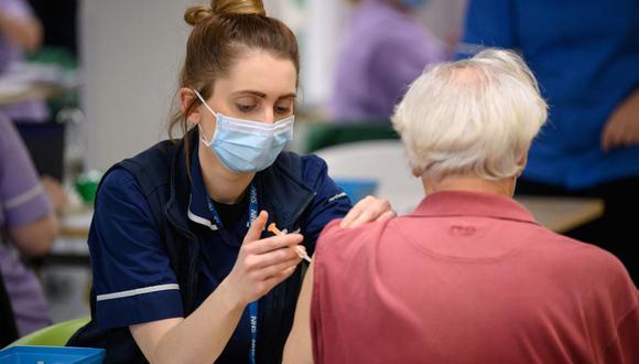Un miembro del equipo médico administra una vacuna contra el coronavirus en el centro de vacunación del NHS, en Robertson House, en Stevenage, al norte de Londres, el 14 de enero de 2021. (Leon Neal / POOL / AFP).