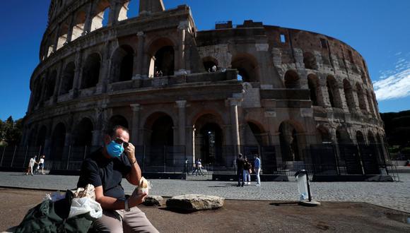 Un hombre con una mascarilla protectora se sienta cerca del Coliseo en Roma (Italia), el 8 de octubre de 2020. (REUTERS/Guglielmo Mangiapane).