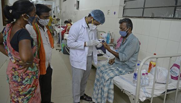Un médico asiste a un paciente con coronavirus con hongo negro, una infección fúngica rara y mortal. (Foto: NOAH SEELAM / AFP)