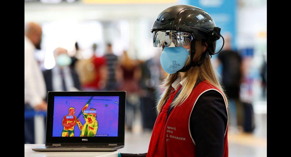 FOTO 3 | La transformación afecta también a los trabajadores de los aeropuertos. En la fotografía, una empleada del Aeropuerto de Roma-Fiumicino (Italia) lleva un casco inteligente que permite medir la temperatura a distancia de los pasajeros. (Foto: Remo Casilli / Reuters).