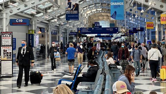 Las personas en el aeropuerto O'Hare de Chicago usan mascarillas el 5 de octubre del 2020. (Photo by Daniel SLIM / AFP)