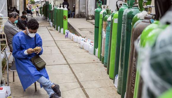 Fotografía tomada en mayo en la ciudad de Iquitos muestra a personas haciendo cola para recargar tanques de oxígeno. (Foto: AFP).