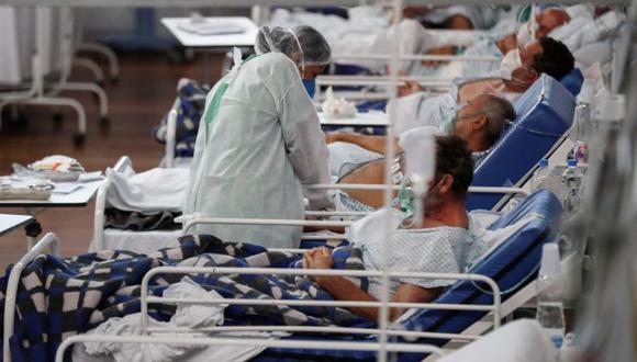 Una trabajadora de la salud atiende a pacientes con la Covid-19, en el Hospital Municipal de Campaña Pedro Dell Antonia, el 15 de abril de 2021 en la ciudad de Santo André, en el estado de Sao Paulo (Brasil). (EFE/ Sebastiao Moreira).