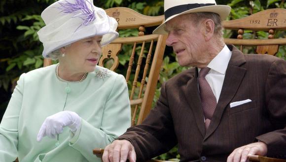 En esta foto de archivo tomada el 17 de julio de 2002, la reina Isabel II (izquierda) y el príncipe Felipe (derecha) conversan sentados durante una actuación musical en Inglaterra. (Fiona HANSON / POOL / AFP).