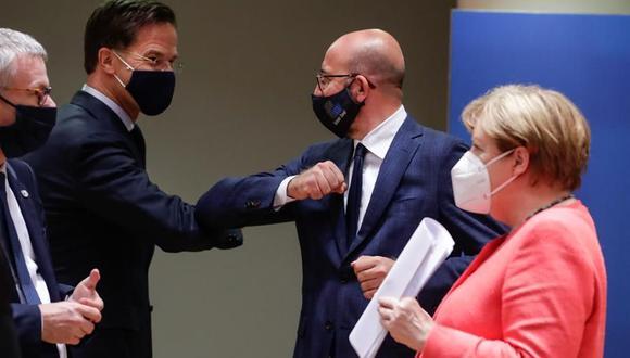El primer ministro holandés Mark Rutte (izquierda) y el presidente del Consejo Europeo Charles Michel se tocan los codos mientras la canciller alemana Angela Merkel observa durante la cumbre de la Unión Europea en Bruselas. (EFE/STEPHANIE LECOCQ).