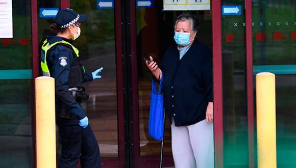 Una policía habla con una residente en un edificio de viviendas públicas de Melbourne puesto en cuarentena por un brote de coronavirus, el 6 de julio de 2020 en la ciudad australiana. (Foto: AFP)