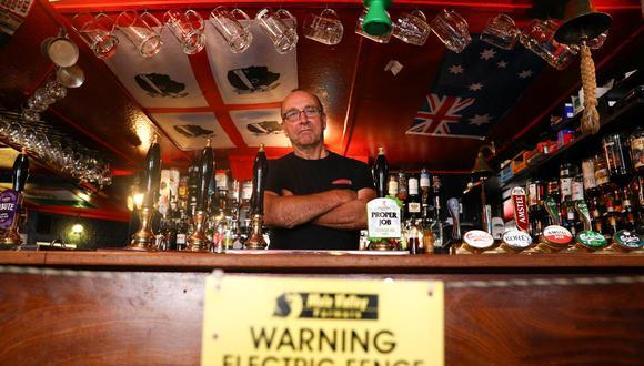 Johnny McFadden, de 61 años, posa para una foto en el bar del The Star Inn, donde se instaló una cerca eléctrica en el área del bar para garantizar que los clientes estén socialmente distanciados del personal al ordenar bebidas, luego del brote de la enfermedad por coronavirus (COVID-19), en St Just, Cornwall, Reino Unido. 14 de julio de 2020. (Foto: REUTERS)