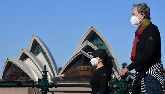 Dos personas pasan por la Ópera de Sídney, Australia, durante el confinamiento para frenar los contagios de coronavirus. (EFE / EPA / MICK TSIKAS AUSTRALIA Y NUEVA ZELANDA).