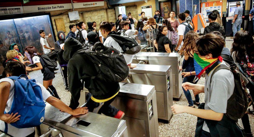 Escolares ingresan al metro de Santiago sin pagar sus pasajes.  AFP
