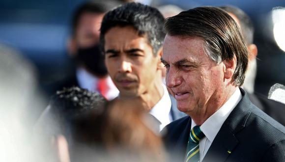El presidente de Brasil, Jair Bolsonaro, habla con simpatizantes durante la ceremonia de izamiento de la bandera nacional antes de una reunión ministerial en el Palacio de la Alvorada, el 27 de octubre de 2020 (Foto de EVARISTO SA / AFP).