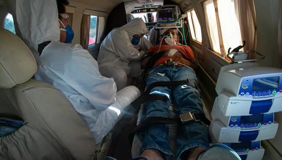 Un paciente de COVID-19 de 47 años recibe tratamiento médico en un avión durante su traslado desde el poblado de Almeirim a la ciudad de Santarem, en el estado brasileño de Pará. (Foto: AFP)