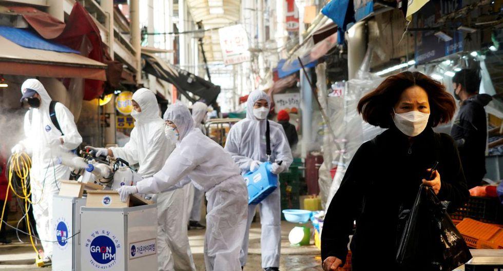 Una mujer con mascarilla camina mientras se produce una fumigación en plena crisis por el coronavirus en Corea del Sur. (Foto: Reuters)