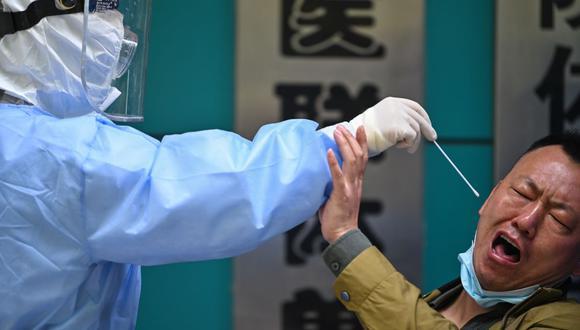 Un hombre al que se le hace la prueba del nuevo coronavirus COVID-19 reacciona cuando un trabajador médico le toma una muestra en Wuhan, China, el 16 de abril de 2020. (Foto de Hector RETAMAL / AFP).