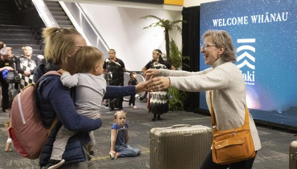 Familiares se reúnen tras el arrivo del primer vuelo desde Sydney, en Wellington, el 19 de abril de 2021, cuando Australia y Nueva Zelanda abrieron una burbuja de viajes sin cuarentena a través de Tasmania. (Foto de Marty MELVILLE / AFP)