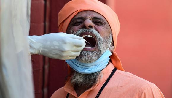 Un funcionario de salud toma una muestra de un hisopo de un hombre para realizar la prueba del coronavirus Covid-19 en un centro de pruebas en Allahabad, India, el 1 de abril de 2021. (Foto de Sanjay KANOJIA / AFP).