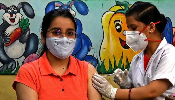 Un trabajador de la salud inocula a una mujer con una inyección de la vacuna contra el COVID-19 de Covishield en un centro de vacunación en Nueva Delhi. (Money SHARMA / AFP)