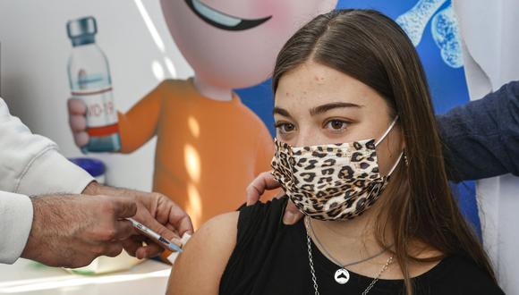 Una adolescente recibe una dosis de la vacuna contra el coronavirus Pfizer-BioNtech en Clalit Health Services, en la ciudad costera mediterránea de Israel de Tel Aviv el 23 de enero de 2021. (JACK GUEZ / AFP).