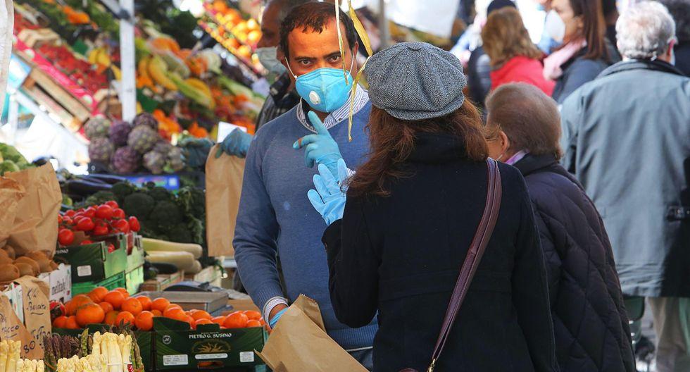 Las personas que usan máscaras faciales protectoras compran en un mercado abierto, en medio del cierre de emergencia por coronavirus, en Padua, Italia. (EFE/NICOLA FOSSELLA).