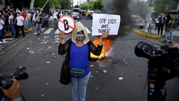 AME3018. SAN SALVADOR (EL SALVADOR), 07/09/2021.- Una mujer posa para los fotógrafos mientras participa en una marcha contra el bitcóin y el Gobierno de Nayib Bukele hoy en San Salvador (El Salvador). La puesta en marcha del bitcóin como moneda de intercambio junto al dólar estadounidense en El Salvador estuvo marcada este martes por la caída del precio de la criptomoneda y el rechazo de cientos de ciudadanos que salieron a las calles a protestar. EFE/ Rodrigo Sura