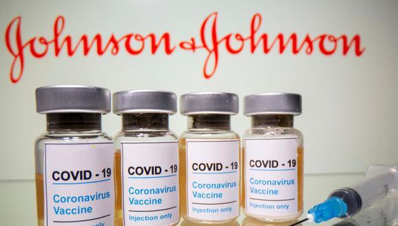 """En esta ilustración tomada el 31 de octubre de 2020, los viales con una etiqueta que dice """"COVID-19 / Vacuna contra el coronavirus / Solo inyección"""" y una jeringa médica son visibles frente al logotipo de Johnson & Johnson. (REUTERS/Dado Ruvic)."""