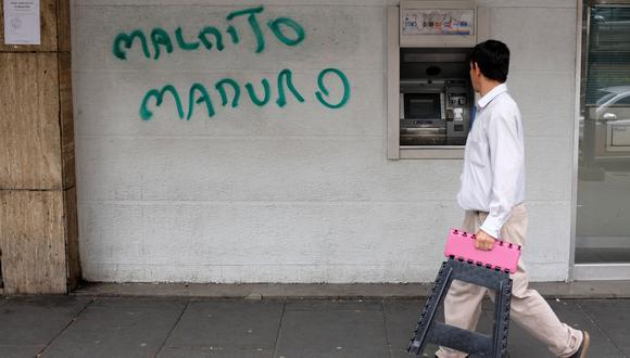 Un hombre pasa al lado de un cajero automático averiado y un mensaje hacia Nicolás Maduro en Caracas. (Foto: Reuters)