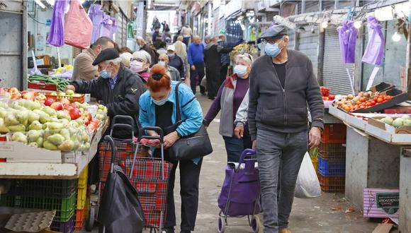 Israelíes, con mascarillas debido a la pandemia de COVID-19, compran en el mercado central de la ciudad costera de Netanya en Israel, el 27 de diciembre de 2020. (JACK GUEZ / AFP).