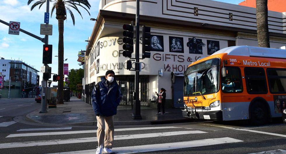 Un hombre usa una máscara facial mientras cruza una calle en Hollywood, California. (Frederic J. BROWN / AFP).