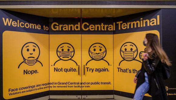 Una mujer con una máscara facial pasa junto a carteles que explican cómo usar una máscara en la estación de tren Grand Central Terminal, el 12 de mayo de 2021, en la ciudad de Nueva York. (Angela Weiss / AFP).