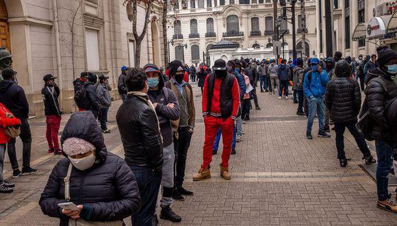 Usando mascarillas protectoras, personas hacen fila fuera de la oficina de una administradora de fondos de pensiones en Santiago, Chile, 27 de julio.