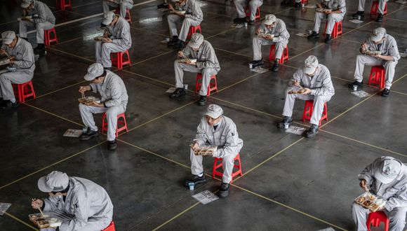 This photo taken on March 23, 2020 shows employees eating during lunch break at an auto plant of Dongfeng Honda in Wuhan in China's central Hubei province. - People in central China, where the COVID-19 coronavirus was first detected, are now allowed to go back to work and public transport has restarted, as some normality slowly returns after a two-month lockdown. (Photo by STR / AFP) / China OUT