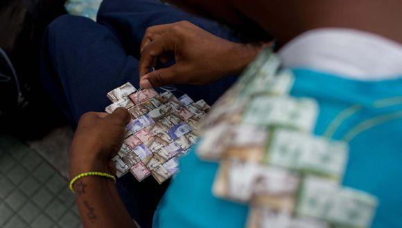 """FOTO 2   2. Hoy utiliza los billetes de 2, 5, 10, 20 y 50 bolívares para realizar bolsos y coronas. """" La gente los tira porque no sirven para comprar nada, ya nadie los acepta"""", dice en las afueras de una estación del tren subterráneo de Caracas, donde vende cigarrillos y café, y pasa el día tejiendo con la devaluada moneda.  (Foto: AFP)"""