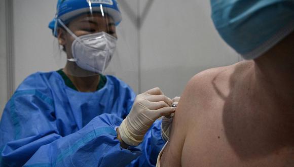 Imagen referencial. Un trabajador médico (izquierda) inocula a un periodista con la vacuna Sinopharm Covid-19 en Beijing  (China), el 15 de abril de 2021. (Noel Celis / AFP).