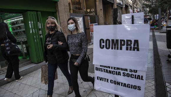 Dos mujeres caminan por el centro de la ciudad de Santiago, el 17 de junio de 2021, durante un nuevo encierro como medida contra la propagación del COVID-19. (Foto: Martin BERNETTI / AFP)