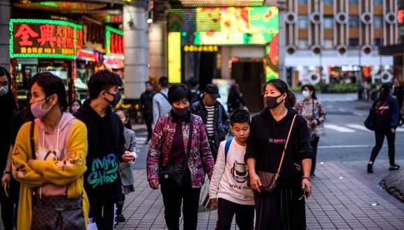 Los peatones usan máscaras faciales mientras caminan por un pavimento en Macao el 22 de enero de 2020, después de que la ex colonia portuguesa reportó su primer caso del nuevo virus similar al SARS que se originó en Wuhan en China. (Fot: AFP)