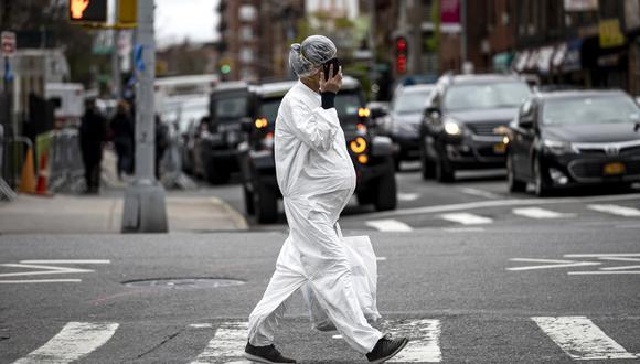 Una mujer embarazada con un traje de materiales peligrosos y una máscara es vista caminando. (Foto: AFP/Johannes Eisele).